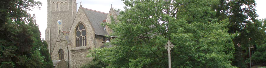 Exterior of church from the high street, through the leafy trees.